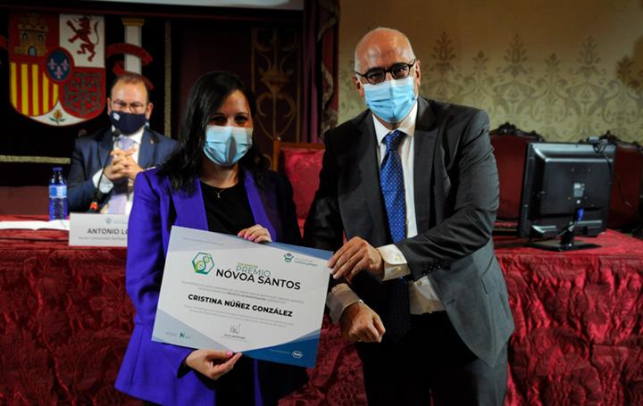 Cristina Núñez recibe el diploma que la acredita como ganadora del Nóvoa Santos en su parte destinada a un proyecto de investigación, de manos de Federico Plaza, Government Affairs director de Roche.